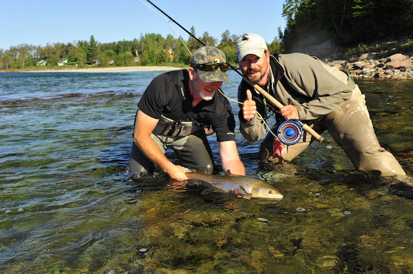 This is a great moment in fly fishing, when an angler and guide taste success, admire a fish, and send it back for another angler to catch some day.